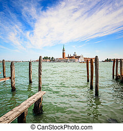 Venice lagoon, wooden poles and church on background. Italy