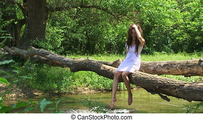 Brunette on a riverside - Curly brunette resting on a...