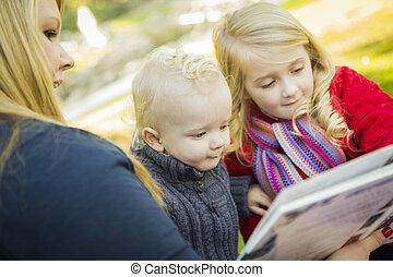 Mother Reading a Book to Her Two Adorable Blonde Children...