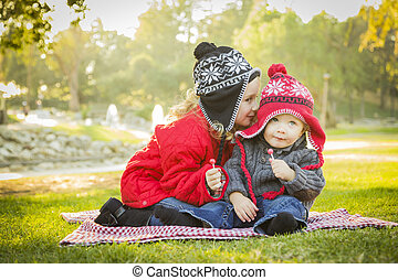Little Girl Whispers A Secret to Baby Brother Outdoors -...