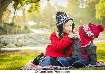 Little Girl with Baby Brother Wearing Coats and Hats...