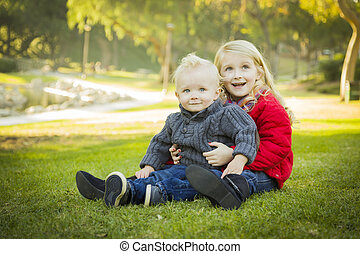 Little Girl with Baby Brother Wearing Coats at the Park -...