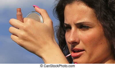 Applying lip gloss - Beautiful woman applying lip gloss