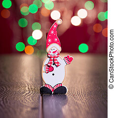 toy snow man with christmas gifts on the background