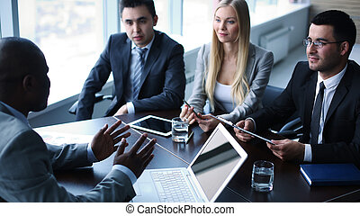Business meeting - Image of business people interacting at...
