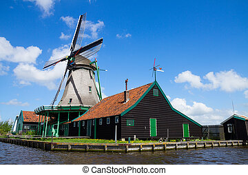 old dutch windmill over river waters - old dutch windmill...