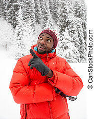 African American Cheerful black man in ski suit in snowy...