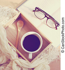 Eyeglasses and book with black coffee on wooden tray, retro...