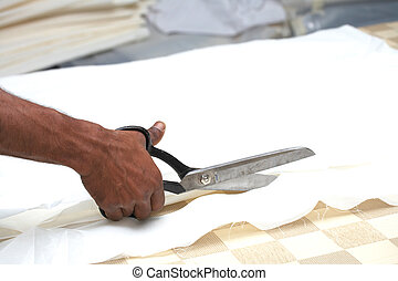 Man cutting fabric - Man cutting white material with...