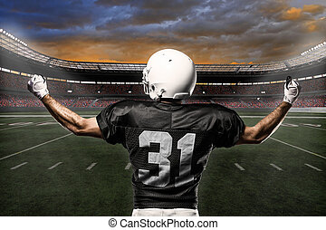 Football Player with a black uniform celebrating on a...