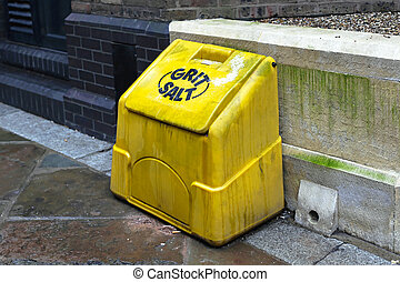 Grit salt yellow plastic box on street pavement