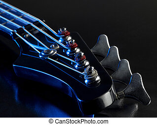 detail of a bass guitar with blue light in black back