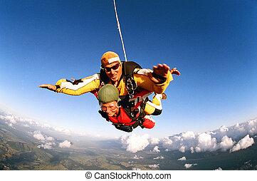 Smiling skydivers mid air - Tandem skydivers smiling in...
