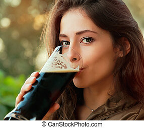 Happy woman drinking dark beer and looking outdoor Closeup...