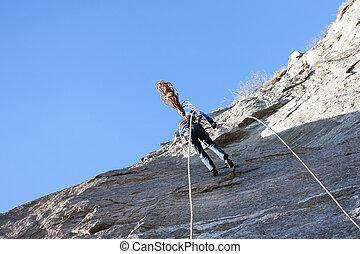 A rock climber abseiling off a climb Italian Alps