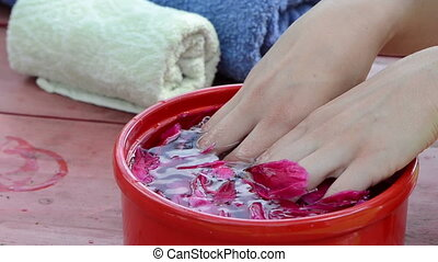 spa for hands - woman remove wet adhering pink peony petals...