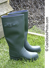 rubber boots - a pair of green rubber boots next to a...