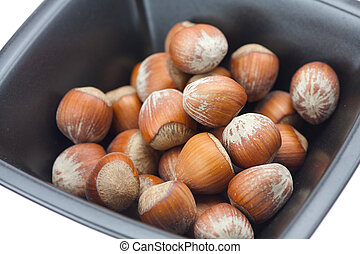 hazelnuts in a bowl isolated on white