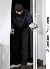 Thief at home - Thief in the balaclava and with crowbar in...