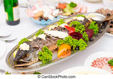 Large stuffed pike with vegetables on the table