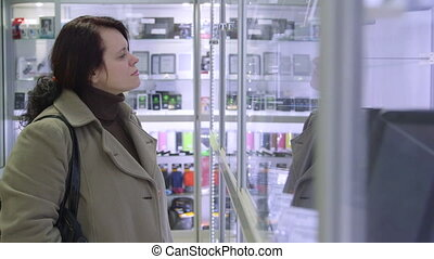 Woman chooses goods in electronics store - Woman chooses...