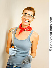 Young woman with hammer in hands - Young woman with hammer...