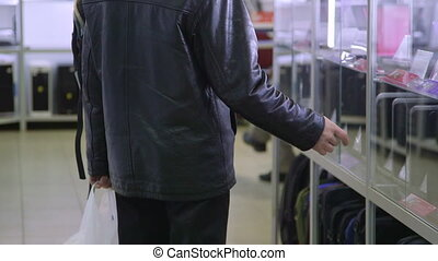 Customers chooses laptop in electronics store