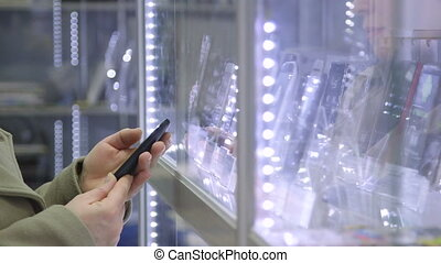 DOLLY: Customer chooses smartphone in electronics store -...