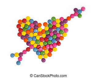 Heart with arrow made of colored smarties on a white...