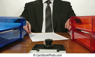 Paperwork Routine - Business person signing and stamping...
