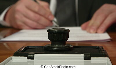 Businessman hand signing and stamping document closeup