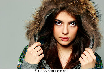 Closeup portrait of a young pensive woman in warm winter...