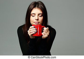 Young happy woman smelling the aroma of coffee