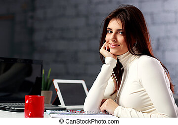 Young businesswoman sitting at the table on her workplace in office