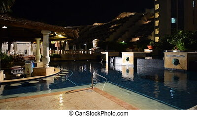 The swimming pool and bar in night illumination at luxury...