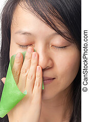 Oily skin - Women with oily skin using oil absorbing sheet...