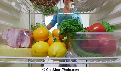 vegetables from the fridge - Housewife takes out fruits and...