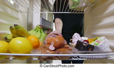reaching for food in refrigerator - Woman reaching for food...
