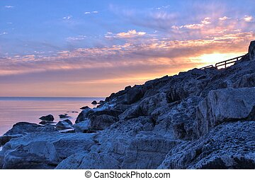 Great Lakes Sunrise - Sun rises over a rocky Great Lakes...