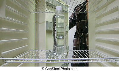 Man takes out a bottle of water from an empty fridge