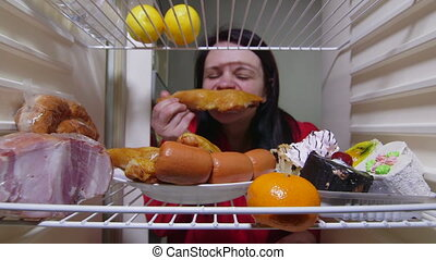 Hungry woman eating fat food inside fridge at night