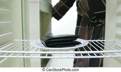 Empty wallet inside the fridge - Man looking for food in an...