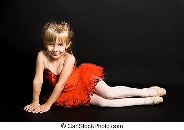 Tiny Ballerina - Young ballet dancer wearing a bright red...