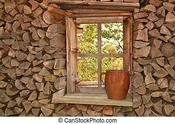 Holzstapel rund um Holzfenster - Brennholz gestapelt um ein...