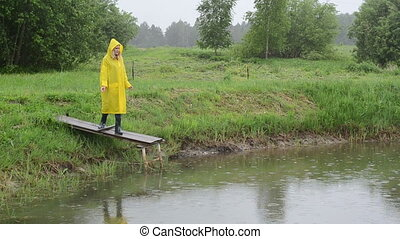 farmer feed fish rain - woman with waterproof coat on small...