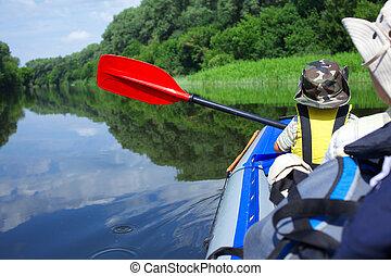 Boy kayaking - Back view of little boy paddling kayak on the...