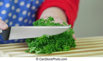 chopped parsley on cutting board - Female hand chopped...