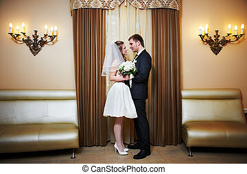 Happy bride and groom look at each other in wedding palace