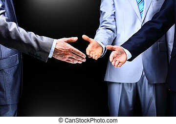 Two business men shaking hands to their leader, close up