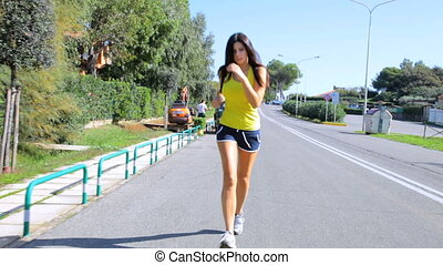Wide shot of jogger on street - Wide shot of woman running...
